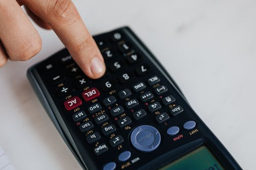 Crop unrecognizable financier using calculator while counting income at work