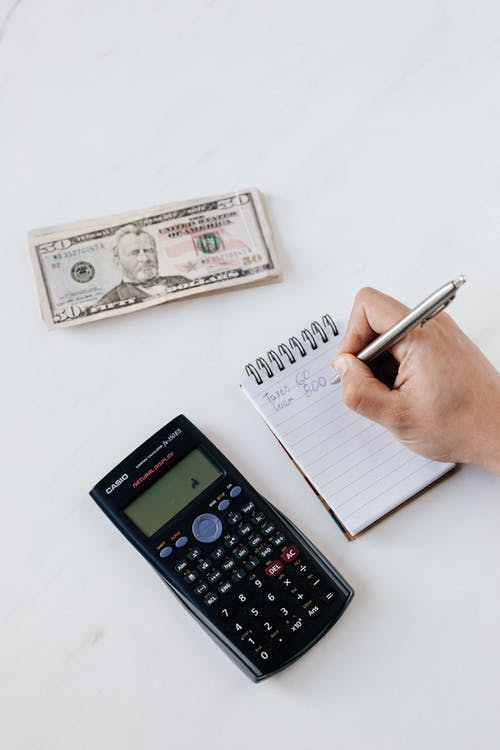 Crop unrecognizable financial worker calculating profit using notebook and calculator