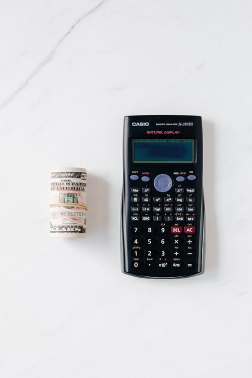 Composition of electronic calculator and roll of greenbacks on table