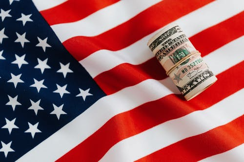 American flag with rolled dollar bills