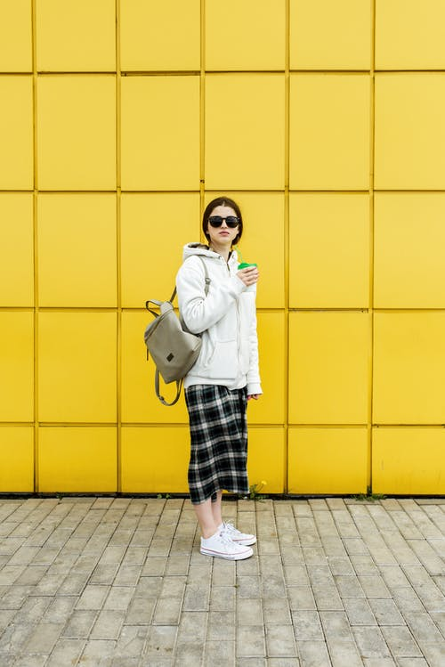 Full body side view of woman in sunglasses and warm wear holding hot drink while standing against yellow wall