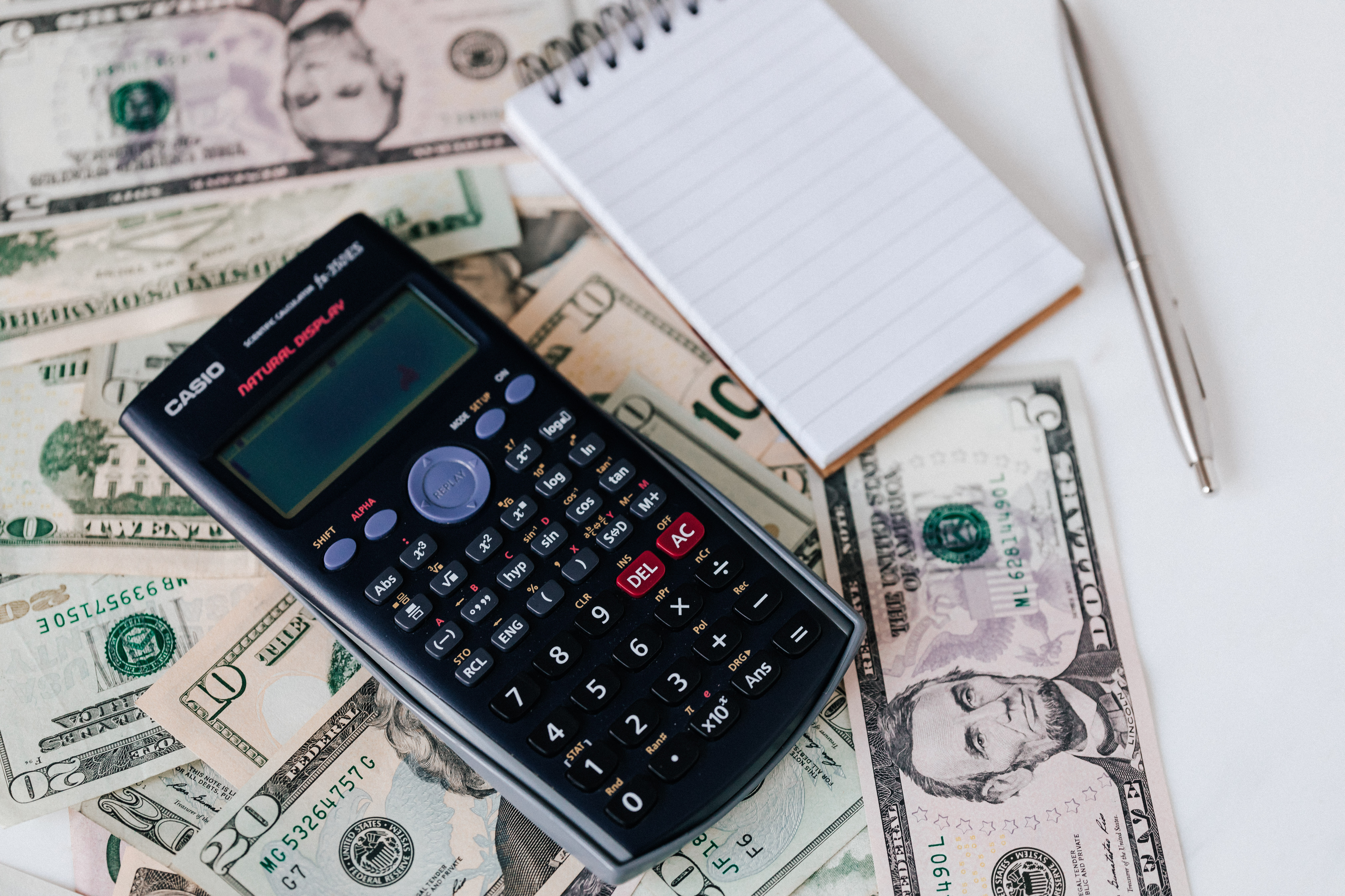 Calculator and notepad placed on USA dollars stack - Hotcopy