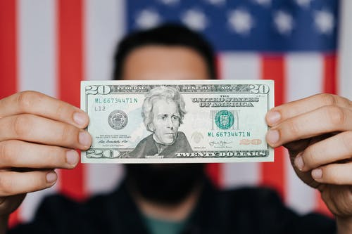 Unrecognizable man showing 20 American dollars