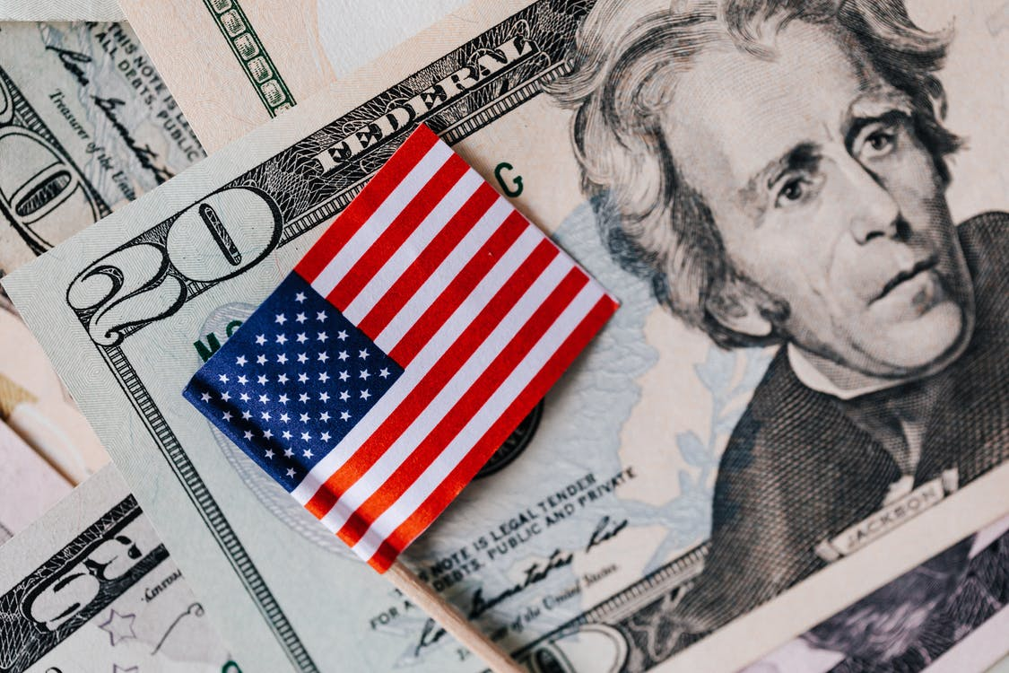 From above of small American flag placed on stack of 20 dollar bills as national currency for business financial operations