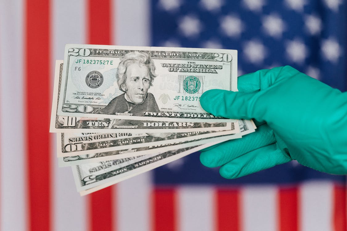 Banknotes of American dollars in hand against flag