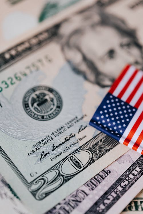 Closeup of small bright American flag placed on various dollar bills