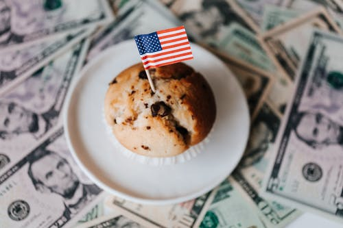 Tasty cake with flag on bunch of paper dollars