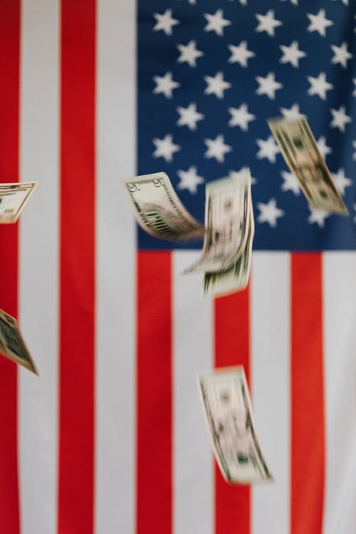 National flag of United States of America on background and dollars falling down