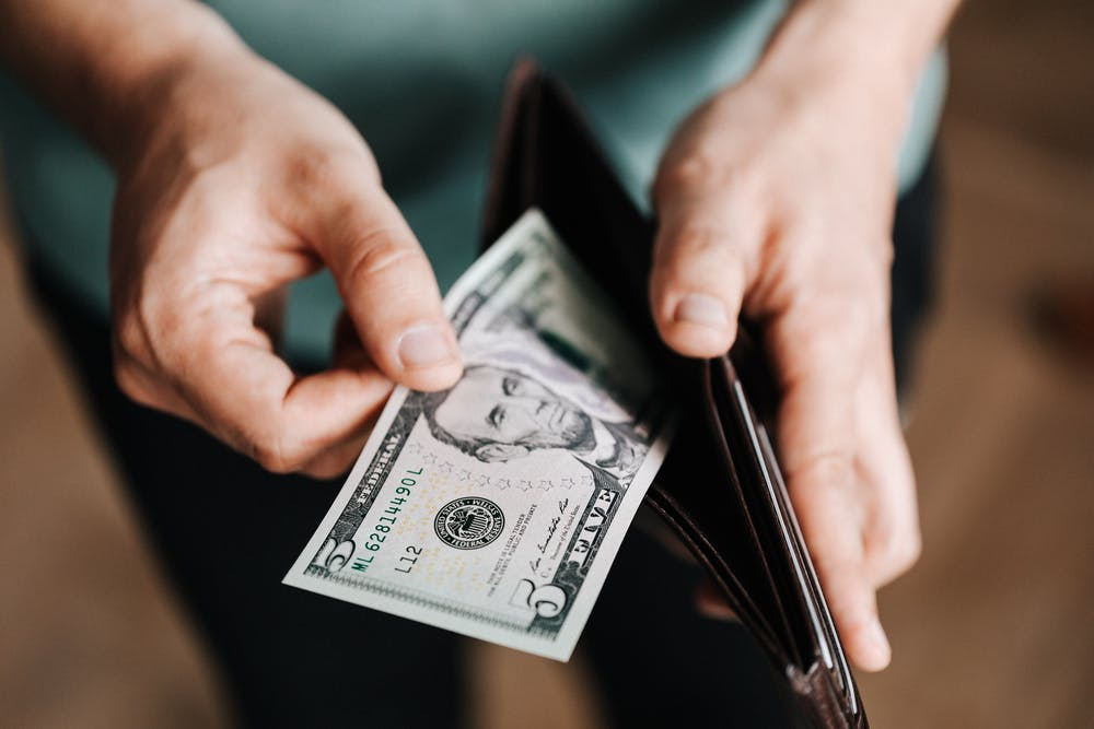 A man holding a wallet with money. | Photo: Pexels