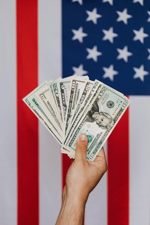 Crop person demonstrating dollars against American flag