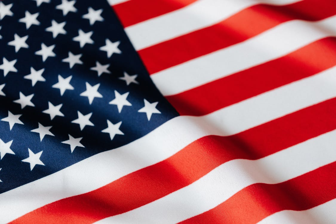 From above of closeup flattering national flag of USA with white and red stripes and stars on blue background