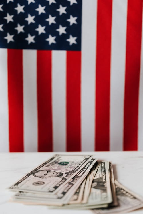 Closeup of dollars pile placed on white surface of table against flag of United States of America