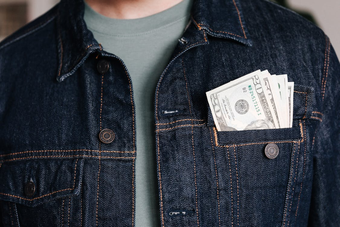 Crop man with dollar banknotes in pocket of jacket