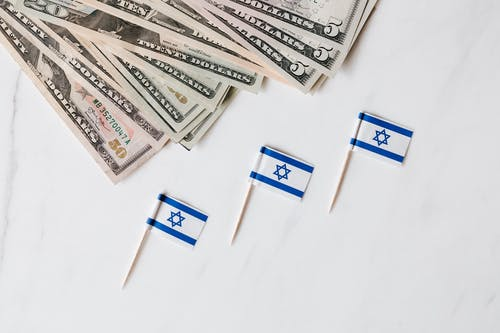 Set of Israeli flags on toothpick and heap of dollars