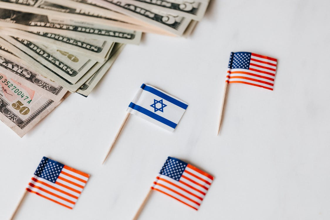 From above closeup of Israeli and American flags on toothpicks and different nominal pars of dollar banknotes on white background