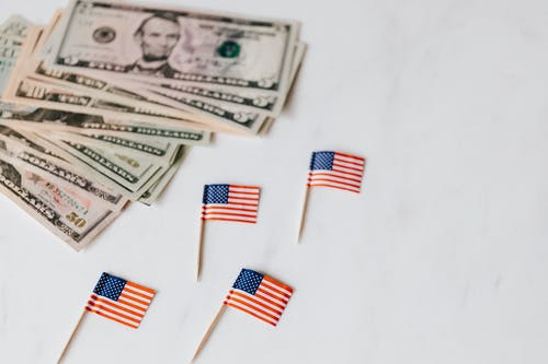 American dollars and national flags on toothpicks on white surface