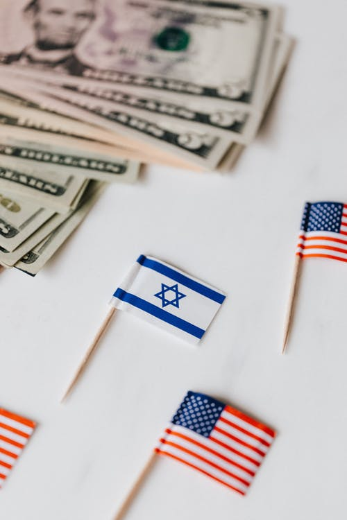 From above set of miniature toothpick flags of USA and Israel placed on white table with dollar banknotes