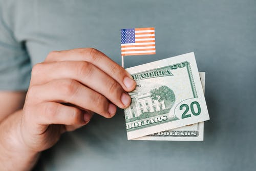 Crop person showing twenty dollar bill and miniature USA flag