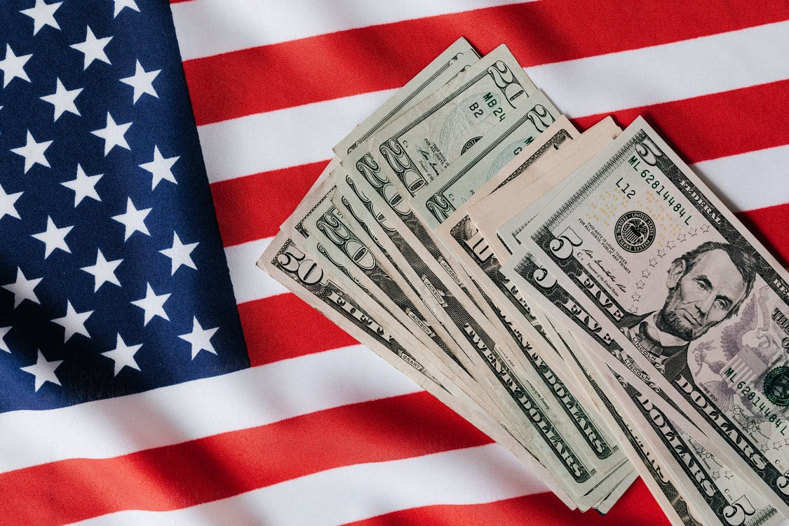 United States flag and pile of dollar bills