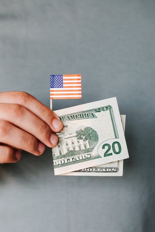 Crop faceless man demonstrating dollar banknote and small USA flag