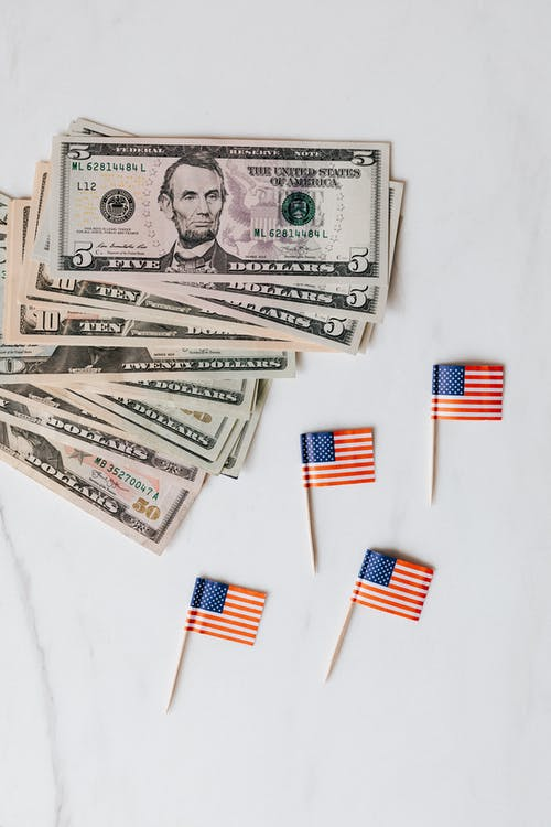 Small paper USA flags placed on white surface with dollars