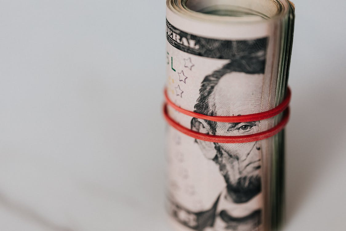 Roll of american dollars tightened with red band