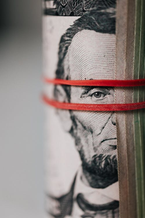Closeup of rolled United States five dollar bills tightened with red rubber band