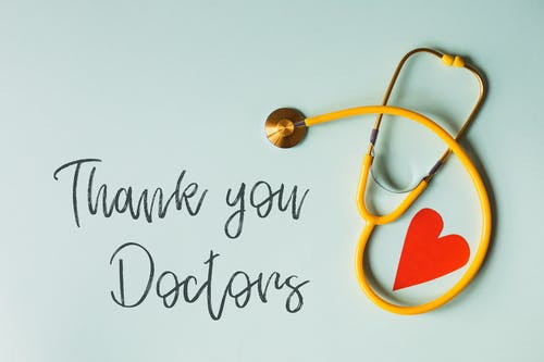 From above arrangement of yellow stethoscope with red heart shape placed on blue background with THANK YOU DOCTORS inscription