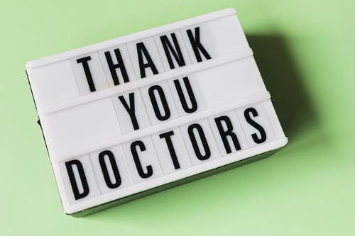 From above of vintage light box with THANK YOU DOCTORS gratitude message placed on green surface