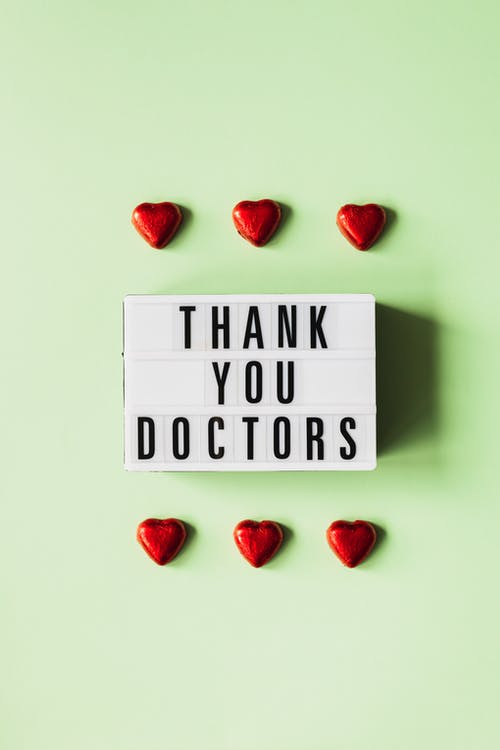 Heart figurines and retro lightbox with inscription for doctors