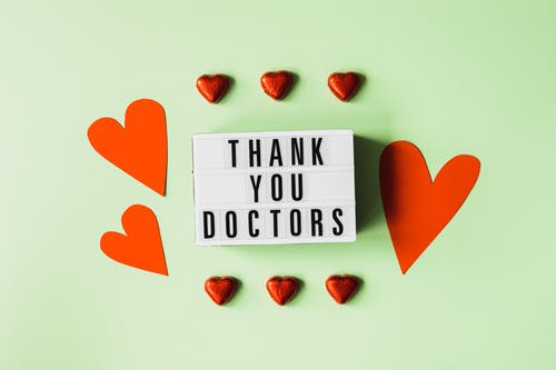 Top view of red heart shaped decorative elements and white retro light box with THANK YOU DOCTORS gratitude message arranged on green background
