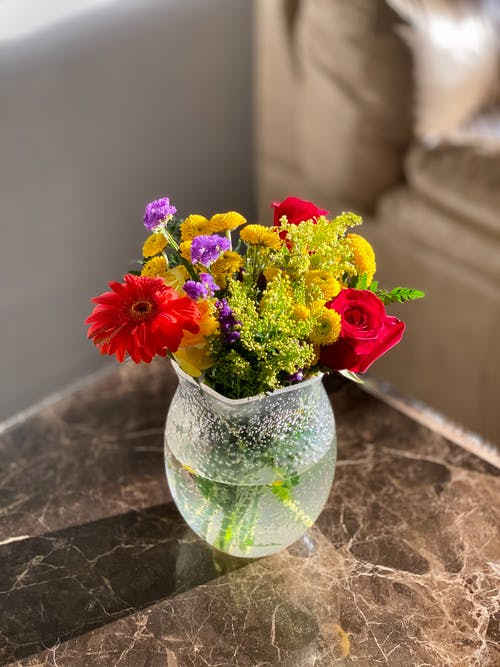 Red and Yellow Flowers in Clear Glass Vase