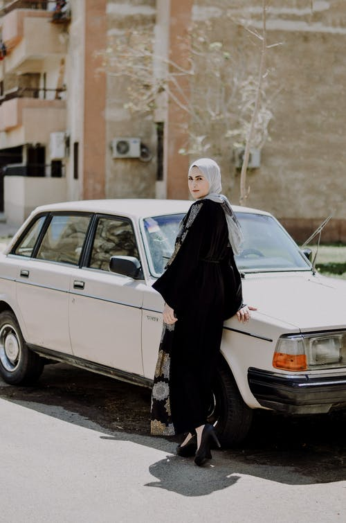 Photo of Woman in Black Abaya While Standing Near White Car