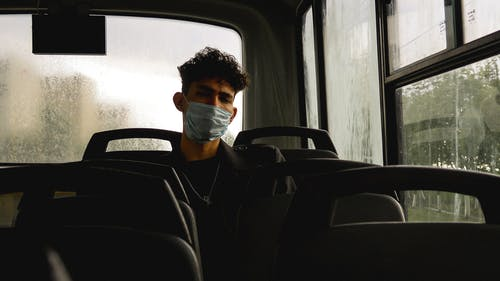 Serious young man in protective mask in bus