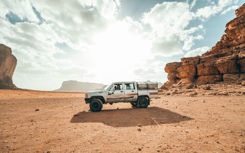 Car driving in desert valley with cliffs