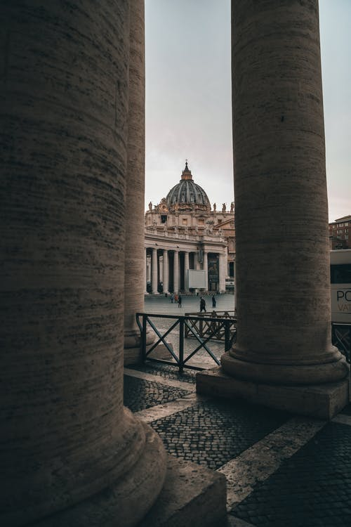 Weathered stone columns located near square with renaissance Cathedral of Saint Paul in Vatican