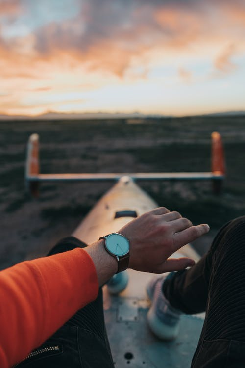 Man checking time on wristwatch in evening