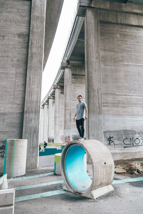 Full length of young man wearing sportswear doing parkour tricks under concrete high bridge