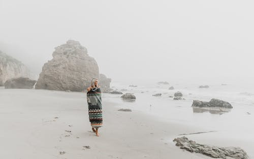 Full body of barefoot female traveler strolling on wet sandy coast against rocky cliff in misty weather