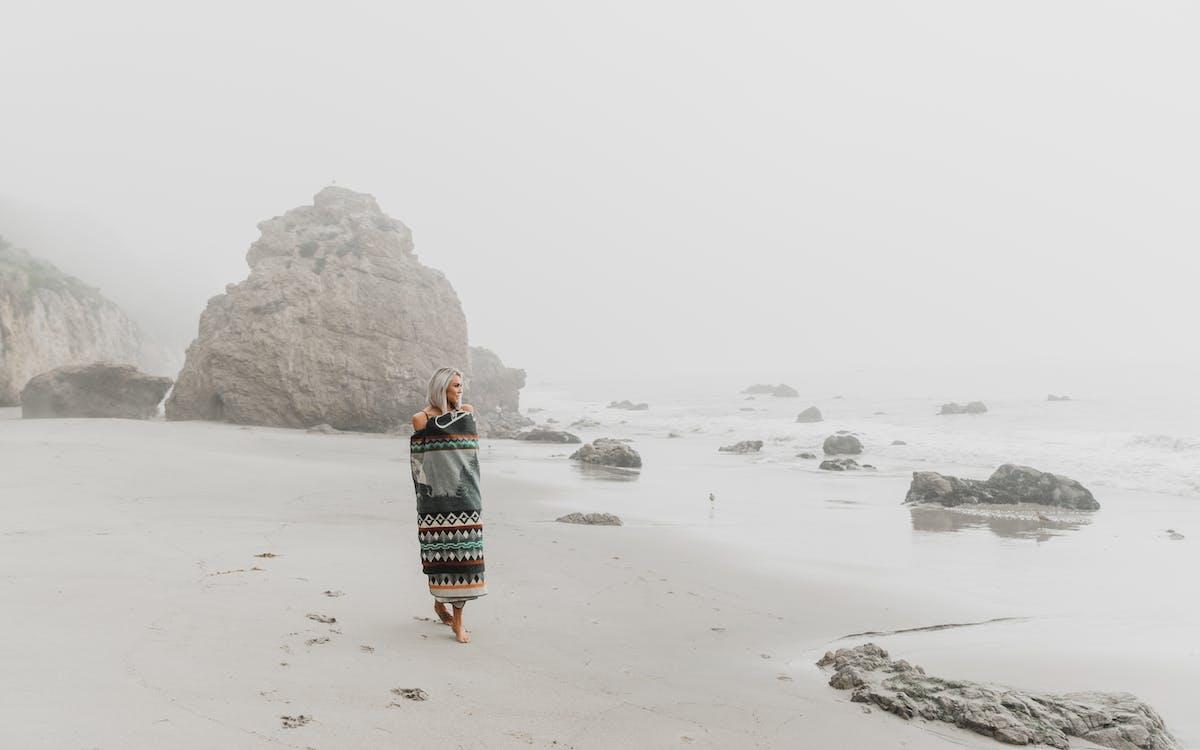 Woman wrapped in blanket walking on sandy shore