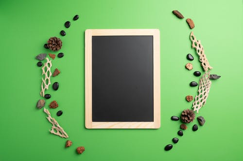Top view of black screen of tablet with bumps and stones around on green background