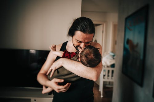 Content ethnic father cuddling and kissing cute toddler while spending time together at home