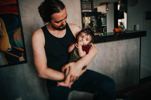 Crop content ethnic father embracing cute baby in apartment