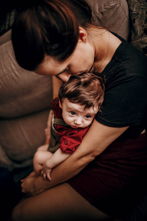 Crop mother kissing baby on comfortable couch at home