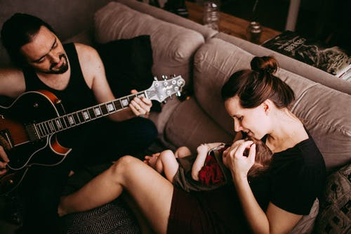 Father Playing Guitar for his Baby and his Wife