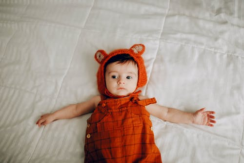 Adorable baby in red wear lying on bed at home