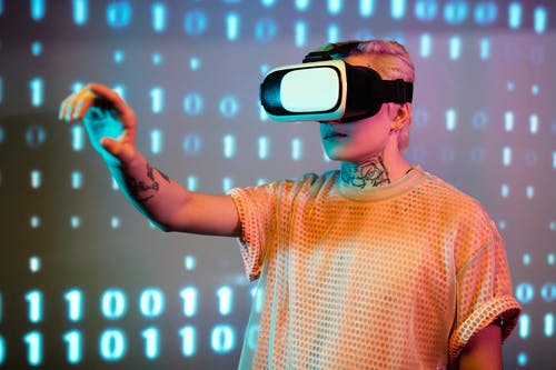 Man in White and Orange Crew Neck T-shirt Wearing White and Black Vr Goggles