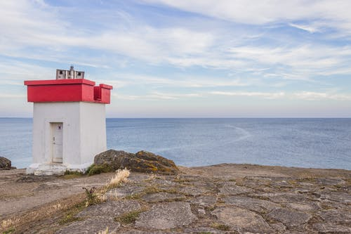 Small lighthouse on dry shore near endless ocean