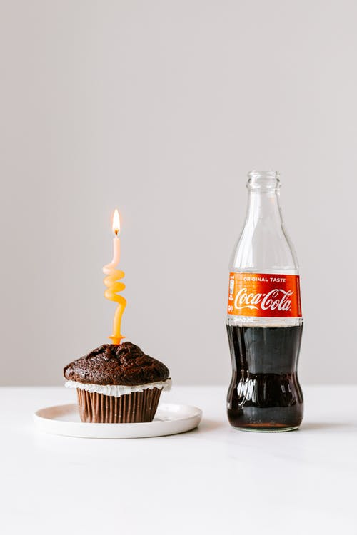 Muffin with burning candle and bottle of coke placed on white table