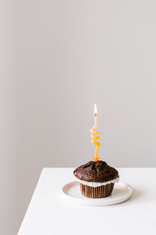 Small cake on plate with lighted candle